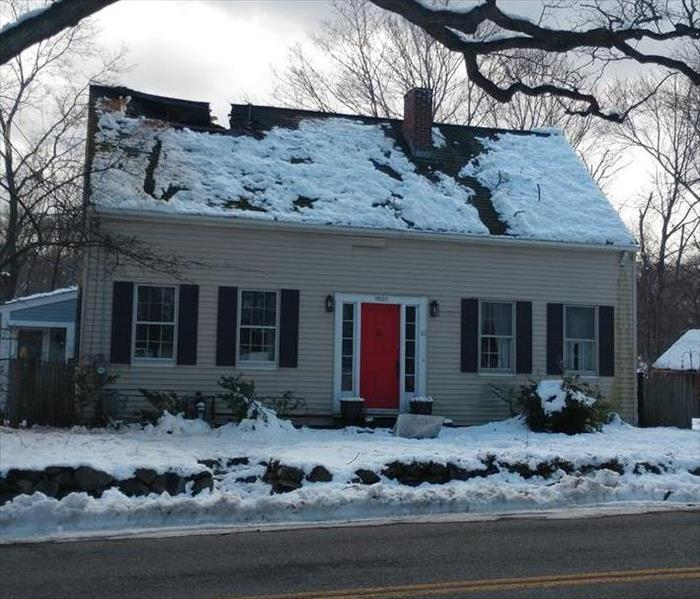 Cape style home covered in snow with badly damaged roof
