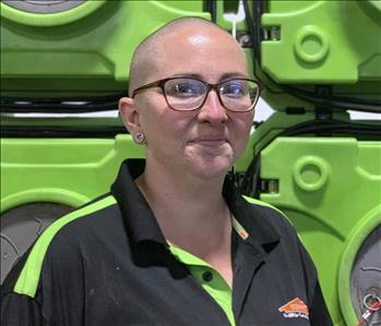 Smiling woman with glasses in SERVPRO uniform standing in front of green equipment