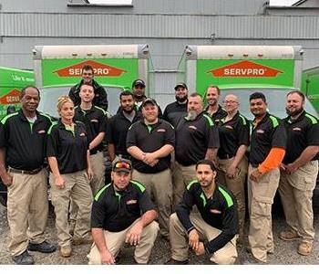 SERVPRO production crew. Smiling employees standing in front of SERVPRO trucks.