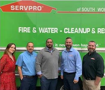 Smiling team, one woman, four men, standing in front of SERVPRO Truck