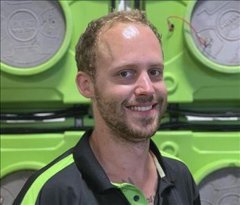 Smiling man with beard ,in SERVPRO uniform in front of green equipment